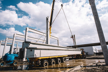 Industrial crane unloading prefabricated cement pillars from cargo