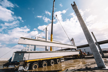 wide angle view of industrial heavy duty crane installing precast cement pillars and cement or concrete beams