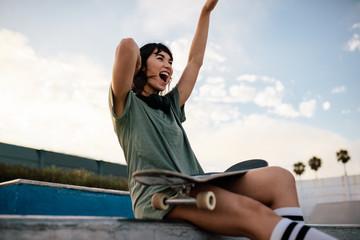 Female skateboarder enjoying herself at skate park