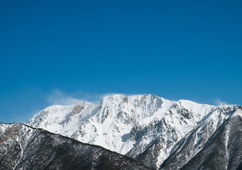 Karachay-Cherkessia mountain peaks in snow against the blue sky and green coniferous forest at the foot of the spring