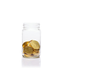 Glass jar with medium amount of  gold coins. Moderate level  of savings.  Savings and wealth management concept
