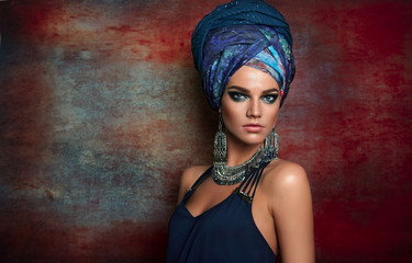 portrait of a beautiful young tanned girl in a blue dress, a tall turban on her head and in silver jewelry on a motley background.