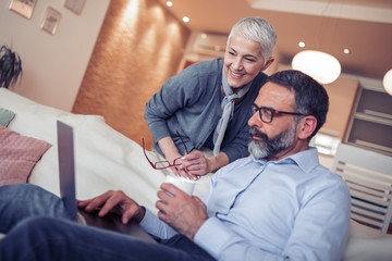 Mature couple using laptop computer at home