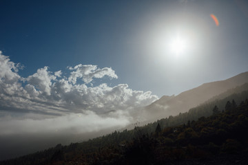 clouds on blue sky with sunshine in mountains