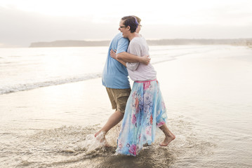 Side view of happy couple embracing while standing on shore at beach