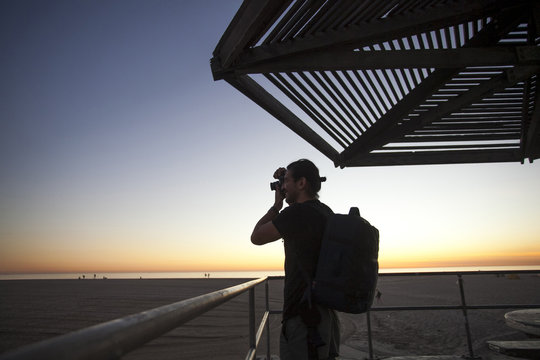 Side view of man taking photograph with camera at beach during sunset