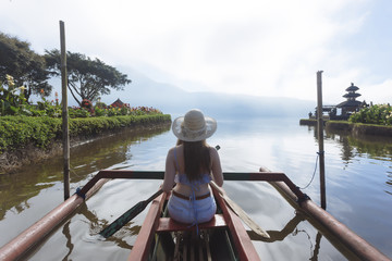 Rear view of woman sitting in boat on lake against cloudy sky