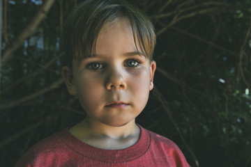 Portrait of boy  standing against trees