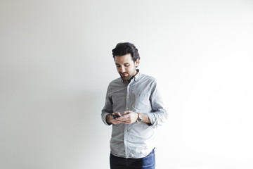 Businessman using smart phone while standing against white wall at office