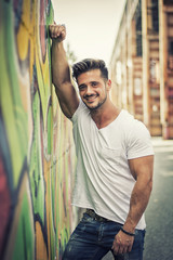Attractive muscle man leaning on colorful graffiti wall, wearing white t-shirt, smiling to camera