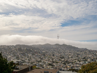 View of fog overtaking Sutro Tower and Twin Peaks in San Francisco