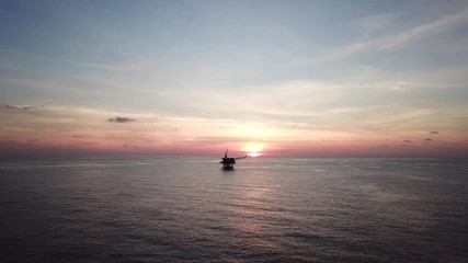 Wall Mural - Aerial view from a drone of a small offshore platform in the middle of the ocean during sunset