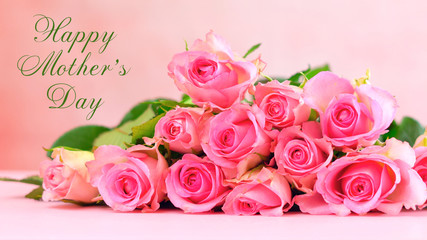 Pink roses on pink wood table, Happy Mother's Day background closeup with greeting message text.
