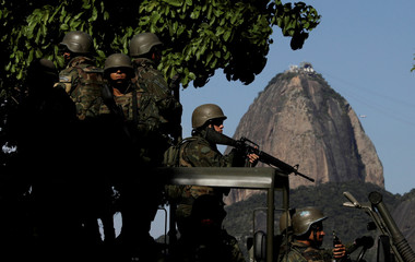 Brazilian marines patrol the streets of Botafogo neighborhood with Sugar Loaf mountain on background in  Rio de Janeiro