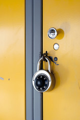 Yellow School Locker with Black Combination Lock - The door of a yellow metal locker in the hallway of a school, locked with a stainless steel combination lock with a black knob on the face.
