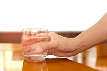 Man hand pick up glass of water on wooden table isolated