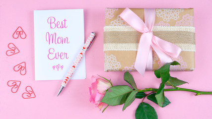 Happy Mother's Day overhead with rose, Best Mom Ever card and gift on pink wood table.