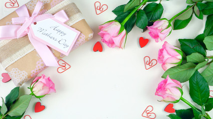 Happy Mother's Day overhead with gift and pink roses on white wood table background with copy space.
