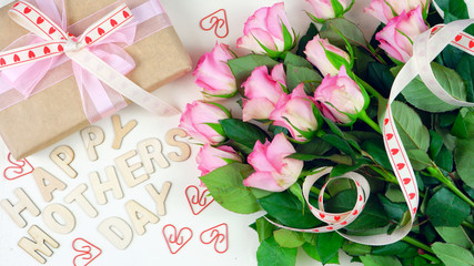 Mother's Day overhead with gift and pink roses on white wood table background with wooden letters spellling Happy Mother's Day.