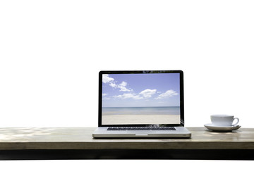 Computer notebook laptop with beach and ocean on screen monitor on wood table Isolated