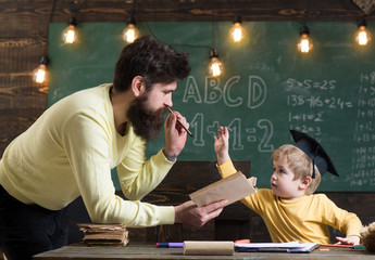 Father, teacher reading book, teaching kid, son, chalkboard on background. Dad wants to grow up genius son. Boy child in graduate cap likes to listening dad. Wunderkind and genius concept.