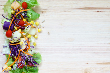 Fresh healthy salad with mixed greens vegetables and fruits on wooden background top view with copy space. Healthy food.