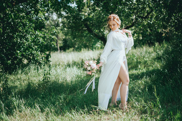 stylish wedding bride with bouquet and amazing modern dress. bride posing and smiling in sunny garden