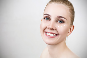 Smiling young woman with cream dots on face.