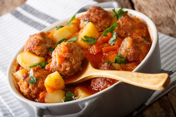 Delicious homemade soup with meatballs close-up in a pot. horizontal