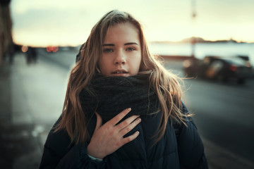 portrait of a girl in a jacket outside in winter against the sunset sky