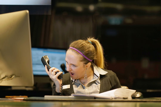 A woman-reception swears with the client of the hotel by phone. A woman is shouting into the phone's phone. Funny facial expressions, emotions, reaction of perception, stress, gilding, nerves.