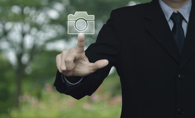 Businessman pressing camera flat icon over blur flower and tree in park, Business camera service concept
