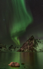 green northern lights (aurora borealis) over fjord with mountain in background