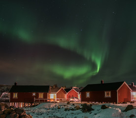 green aurora borealis (northern light) over typical scandinavian red cabins