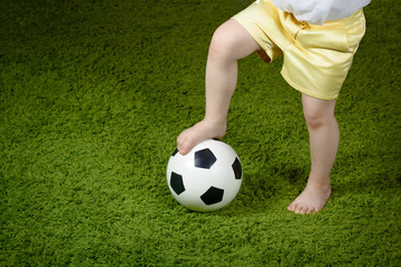 A little girl in shorts put her foot on a soccer ball on a green surface. Copyspace