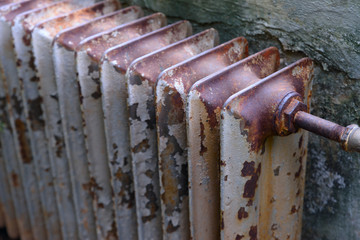 Old obsolete rusty radiator. The problem of winter house heating. Cold, poor heating in old housing.