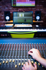 sound engineer hands working on audio mixing console in recording studio