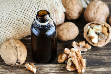 Walnut  natural oil  in small bottle and  raw walnuts  on wooden table. Organic and natural skin care concept.