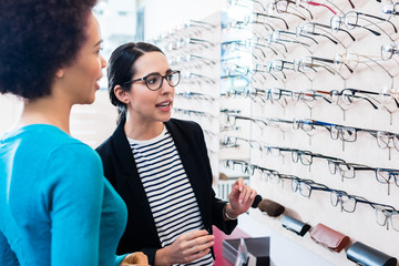 Cheerful black woman inspecting glasses in optician shelf