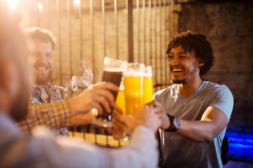 Young excited multicultural men celebrating and toasting with a beer in the sunny pub after work.