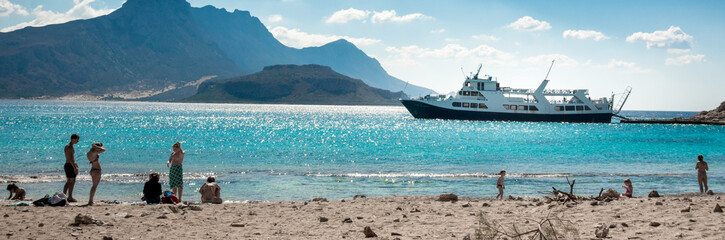 Beach with cruise ship and mountain, Crete, Greece