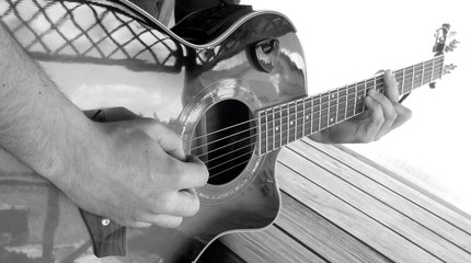 A man plays an acoustic guitar with two hands close-up picture black and white photography