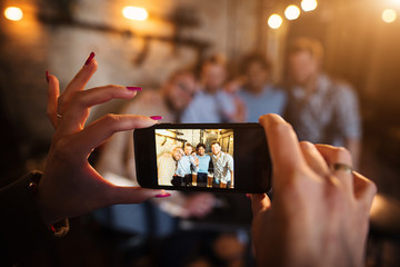 Close up focus view of woman hands and mobile while taking a photo of four happy friends relaxing in the pub.