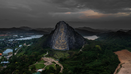 Aerial view of carved buddha image from gold on the cliff at Khao Chee chan durinh cloudy day, Pattaya in Thailand