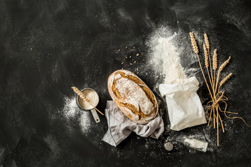 Bread, flour bag, wheat and measuring cup on black