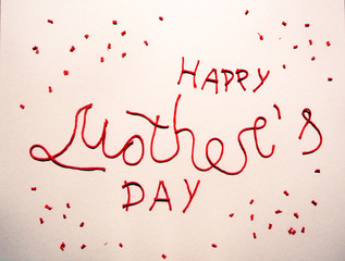 picture of the inscription Happy Mother's day made by red threads on beige background. Hand lettering. Cute text for postcard.