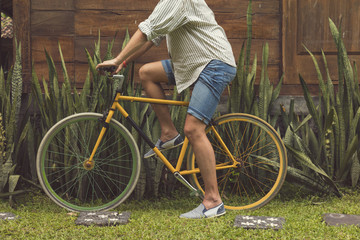 Handsome attractive man riding old bicycle outdoors.