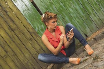 Cute woman using smart phone outdoors.