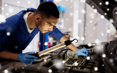 car service, repair, maintenance and people concept - auto mechanic man with lamp working at workshop over snow