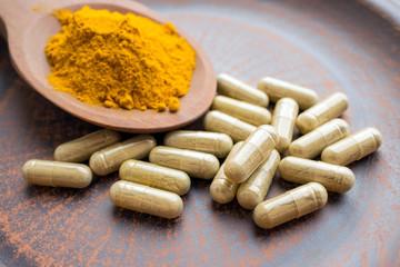 Natural herb food supplement turmeric veggie capsules and spoon with orange curcumin powder on clay plate.  Organic Turmeric extract, Curry Extract, Diferuloylmethane, JiangHuang, Curcuma Longa